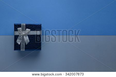 Blue Gift Box With Silver Bow On Two-tone Monochrome Trendy Classic Blue Paper Background Top View B