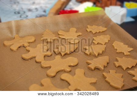 Raw Dough In The Form Gingerbread Cookies Of Christmas Trees And Little Men Lie On Baking Paper Clos