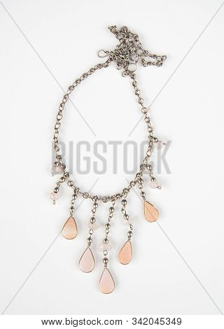 Coral Pink Quartz Necklace Jewelry Isolated On A Light Background.  Silver Chain With Gemstone Teard