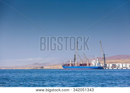 Paracas, Peru - 2019-12-05. A Large Cargo Ship Stands In Port On Loading Off The Coast Of The Ocean,