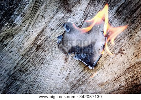 Shallow focus Kraft paper heart on fire on a wooden background, focus on top edge of heart and ash, kraft paper has texture from the paper