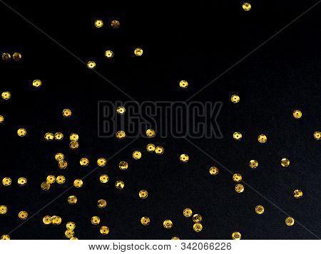 Golden Paillette Glitter On Black Background. Festive Holiday Bright Backdrop