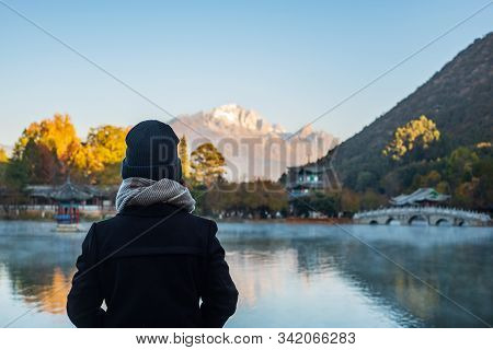 Young Woman Traveler Traveling At Black Dragon Pool With Jade Dragon Snow Mountain Background, Landm