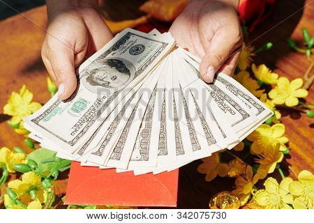 Person Holding Money For Traditional Red Envelopes For Tet Holiday