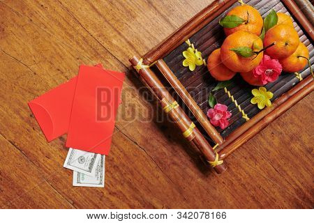 Bamboo Tray With Fresh Tangerines And Traditional Red Envelopes With Money For Tet Celebration, View