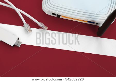 Latvia Flag Depicted On Table With Internet Rj45 Cable, Wireless Usb Wifi Adapter And Router. Intern