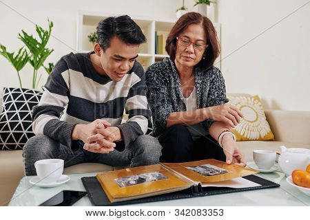 Mature Asian Woman Showing Album With Old Black And White Photos To Her Teenage Son