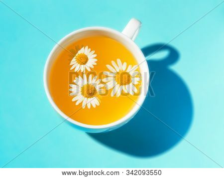 Herbal Tea With Fresh Chamomile Flowers In A White Cup. Cup Of Medicinal Chamomile Tea On A Bright T