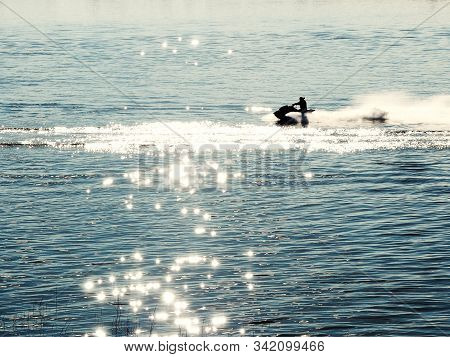 Silhouette Of Man Drive Jet Ski At Sunset. Sport Activity On Beach Holiday