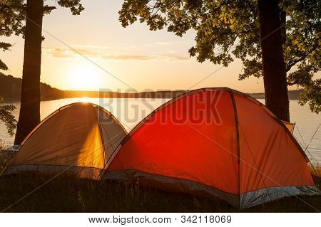 Bright Tents On Primitive Campsite By The Picturesque Lake At Sunset