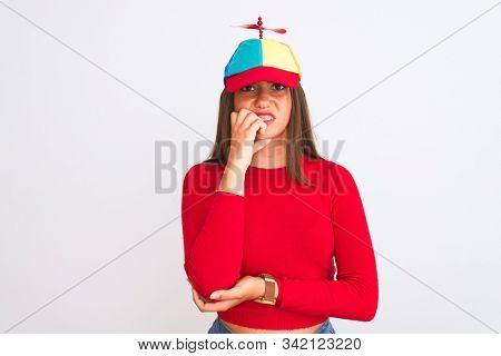 Young beautiful girl wearing fanny cap with propeller standing over isolated white background looking stressed and nervous with hands on mouth biting nails. Anxiety problem.