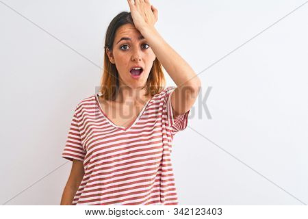 Beautiful redhead woman wearing casual striped red t-shirt over isolated background surprised with hand on head for mistake, remember error. Forgot, bad memory concept.