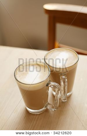 coffee latte in two tall glasses woden table and chair