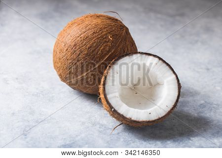 Cracked Fresh Coconut  And Slice Nut On Concrete Background, Space For Text Food Ingredients, Health