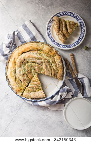 Greek Pie Spanakopita  Over Concrete  Background. Ideas And Recipes For Vegetarian Or Vegan  Spinach
