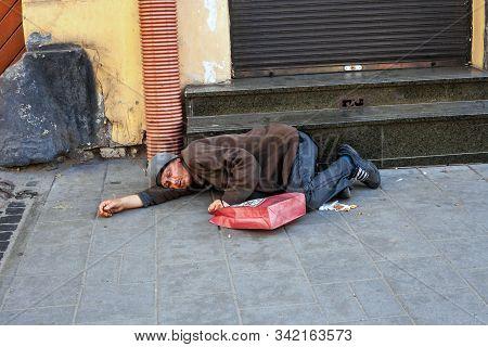 Lviv, Ukraine - 26 October 2019: Drunken Homeless Man Sleeping On City Street Near Shop Staircase