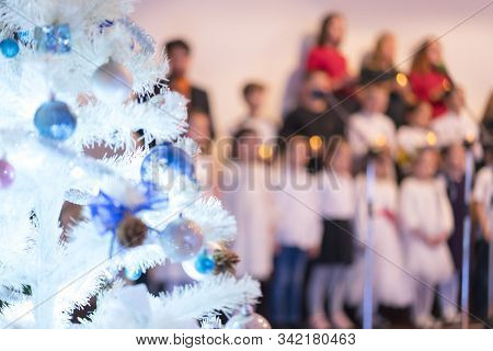 Childrens New Years Choir. Christmas Tree And Childrens Choir. Christmas And New Year Concept. Blurr