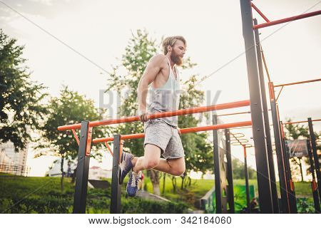 Fit Man Workout Out Arms On Dips Horizontal Bars Training Triceps And Biceps Doing Push Ups. Handsom