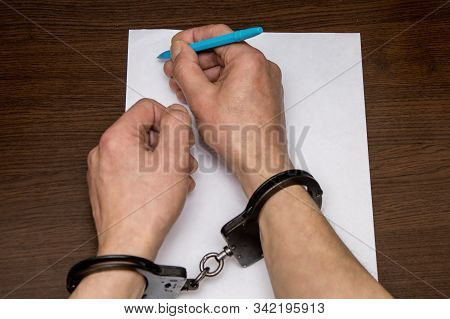 A Man With Bare Hands In Handcuffs Sits At A Table In Front Of A Blank Sheet Of Paper And A Fountain