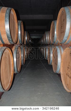 Bento Goncalves, Brazil - July 11, 2019. Corridor With Several Wood Barrels For Storage And Wine Agi