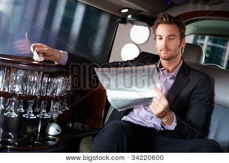 Handsome young man sitting in limousine, reading newspaper.