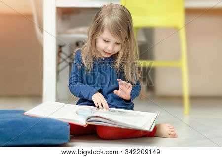 Little Fair-haired Girl Examines Illustrations In A Childrens Book Sitting On The Floor At Home. Ear
