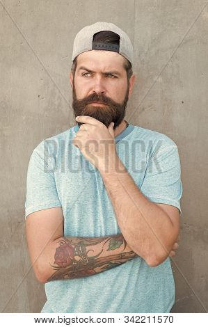 To Beard Or Not To Beard. Thoughtful Hipster Thinking On Grey Wall. Hipster Touching Thick Beard Hai