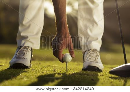 Golfers Hand Placing Golf Ball Onto Tee Close Up With Blurred Feet And Flare Background