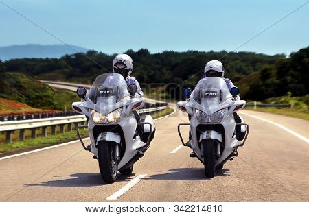 Highway Patrol Policeman On Motorbike Under Bright Sunlight