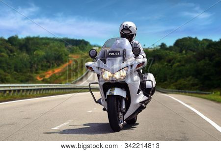 Highway Patrol Policeman On Motorcycle On Bright Daylight
