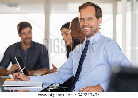 Portrait of smiling businessman at conference with his team in background. Successful business man looking at camera in the meeting room while colleagues working behind. Handsome middle aged formal.