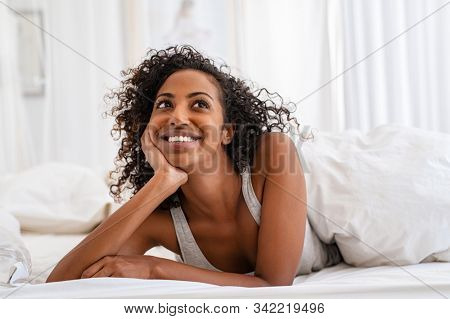 Happy pensive young woman lying and thinking on bed in bedroom. Thoughtful african girl in pajamas lying on bed while looking up with copy space. Smiling black woman contemplating the future at home.