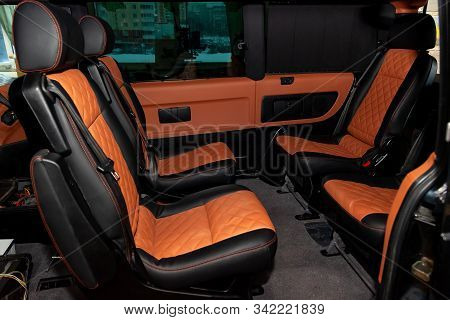 Four Rear Seats In A Minibus Are Deployed To Each Other And Tightened In Black And Brown Leather Wit