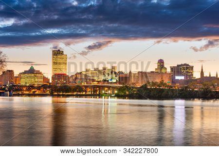 Albany, New York, USA skyline on the Hudson River at sunset.