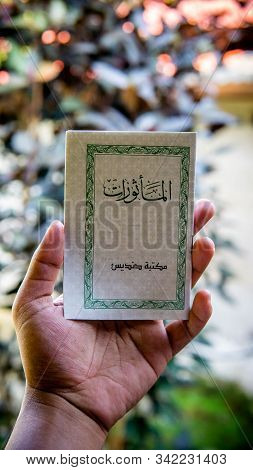 Hand Holding A Mini Book Written Al-mathurat In Arabic Word. It Is A Compilation Of Few Verses From