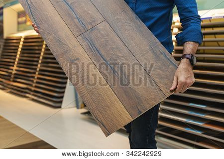 Flooring Store Salesman With Laminate Floor Sample Panel In Hands