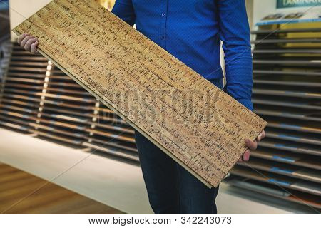 Flooring Shop Salesman With Laminate Floor Sample Panel In Hands