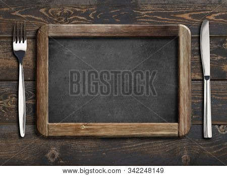 menu blackboard frame on old wooden dinning table with knife and fork