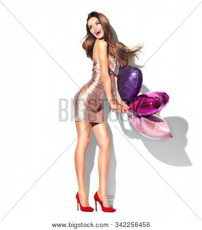 Valentine Beauty girl holding colourful air balloons, laughing, isolated on white background. Beautiful Happy Young woman, holiday party. Joyful model posing, having fun, celebrating Valentine's Day