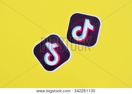 Tiktok Paper Logo On Yellow Background. Tiktok Is A Popular Video-sharing Social Networking Service