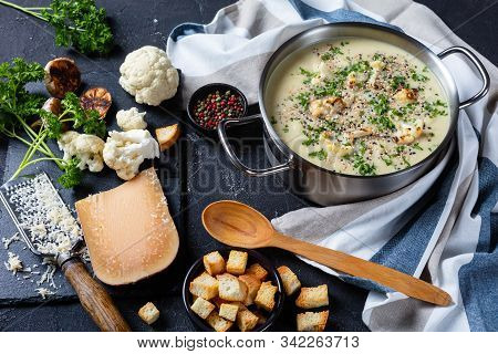 Close-up Of Asiago Roasted Garlic Cauliflower Soup  In A Stockpot With Ingredients And Croutons On A