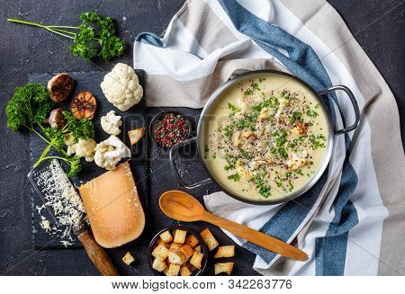 Asiago Roasted Garlic Cauliflower Soup  In A Stockpot With Ingredients And Croutons On A Concrete Ta