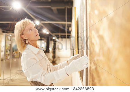 Side View Portrait Of Elegant Mature Woman Hanging Paintings While Working In Art Gallery Or Museum,