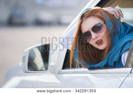 Young Woman Driving A Car Backwards. Girl With Funny Expression On Her Face While She Made A Fender