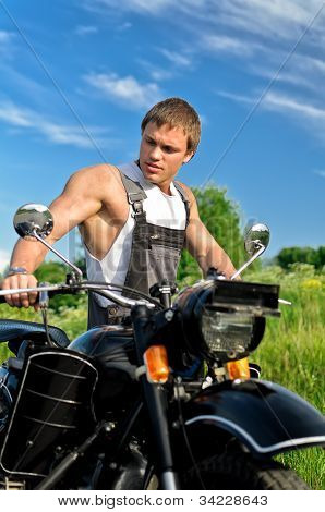 Handsome Man In A Boilersuit Standing Near Motorcycle.
