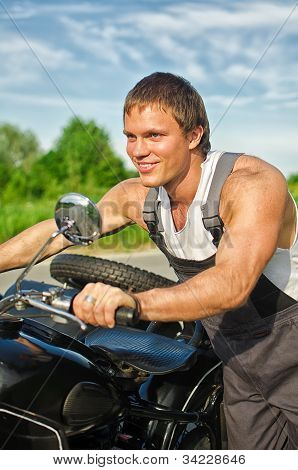 Portrait Of Handsome Mechanic Pushing A Motorcycle