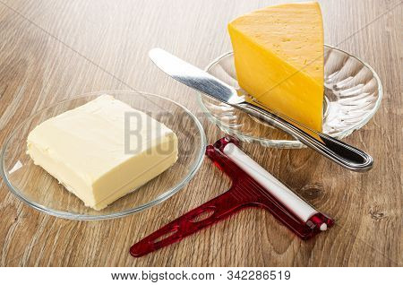 Butter In Transparent Saucer, Cheese And Knife In Saucer, Cheese Cutter On Wooden Table