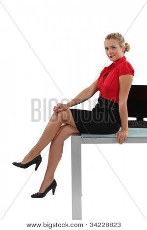 Leggy businesswoman sitting on her desk