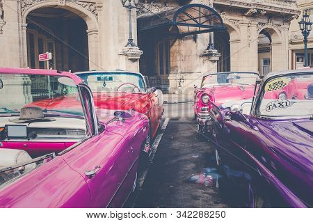 Havana, Cuba - December 21, 2019: Vintage Colored Classic American Cars Front Of The Galician Palace