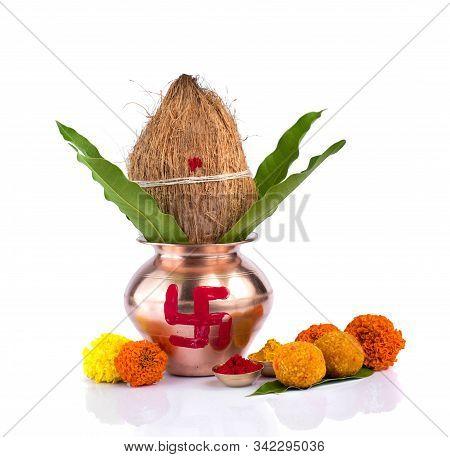 Copper Kalash With Coconut, Mango Leaf, Haldi, Kumkum And Sweets With Marigold Flower Decoration On